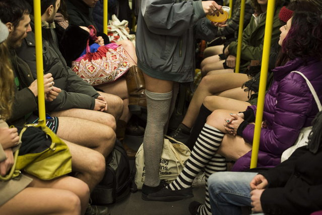 """People taking part in the """"No Pants Subway Ride"""" are seen on the U2 Subway line in Berlin on January 12, 2014. (Photo by Odd Andersen/AFP Photo)"""
