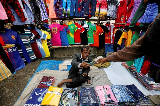 A street vendor returns change money to a customer after selling ready-made garments in Dhaka, Bangladesh January 17, 2017. (Photo by Mohammad Ponir Hossain/Reuters)