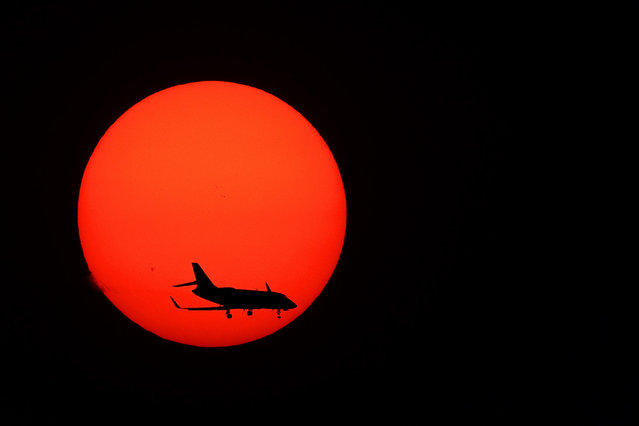 A plane on approach to Long Beach Airport passes in front of a setting sun on September 23, 2021 in Huntington Beach, California. Wildfires in the area have caused smoky conditions in parts of southern California. (Photo by Michael Heiman/Getty Images)