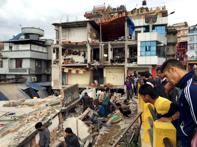 People survey a site damaged by an earthquake, in Kathmandu, Nepal, April 25, 2015. (Photo by Navesh Chitrakar/Reuters)