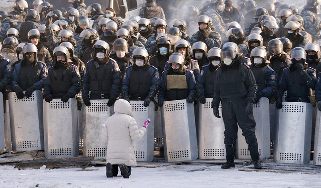 A woman speaks as she kneels down in front of a line of riot police in the center of Kiev on January 24, 2014. Ukrainian protesters today expanded their protest camp in Kiev closer to the administration of President Viktor Yanukovych, after crisis talks to end Ukraine's worst crisis since its 1991 independence ended in deadlock. (Photo by Sergei Supinsky/AFP Photo)