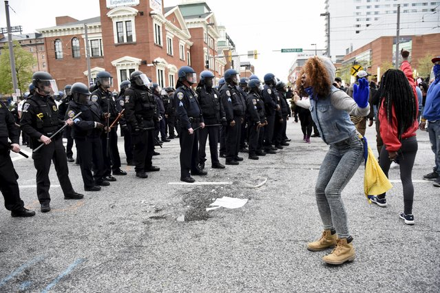 A demonstrator gestures towards police near Camden Yards during a protest against the death in police custody of Freddie Gray in Baltimore April 25, 2015. (Photo by Sait Serkan Gurbuz/Reuters)