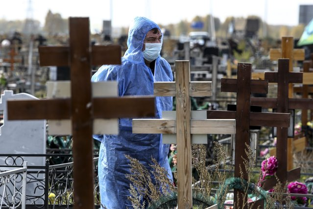 A grave digger wearing a protective suit stands during a a COVID-19 victim burial at a cemetery outside in Omsk, Russia, Thursday, October 7, 2021. Russia's daily coronavirus infections have soared to their highest level so far this year as authorities have struggled to control a surge in new cases amid a slow pace in vaccinations and few restrictions in place. The daily coronavirus death toll topped 900 for a second straight day with 924 new deaths reported Thursday. Russia already has Europe's highest death toll in the pandemic and a conservative way of calculating the number suggests the actual number could be even higher. (Photo by AP Photo/Stringer)