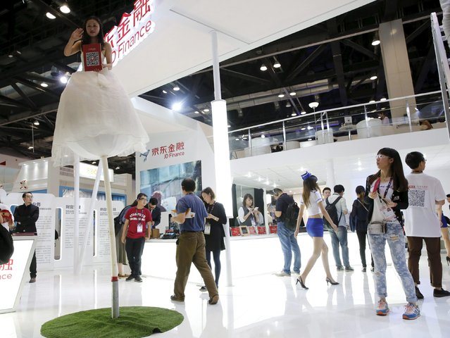 A promotional staff stands on a pole as part of an installation depicting a flower, at JD Finance's booth at the Global Mobile Internet Conference (GMIC) 2015 in Beijing, China, April 28, 2015. (Photo by Kim Kyung-Hoon/Reuters)