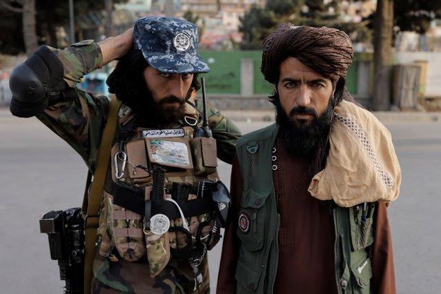 Members of Taliban forces, of which one is armed, pose at a check point after several civilians were killed in an explosion, in Kabul, Afghanistan October 3, 2021. (Photo by Jorge Silva/Reuters)