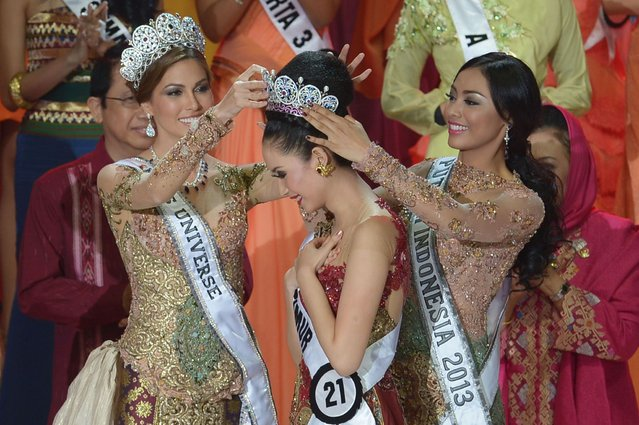 This picture taken in Jakarta on January 29, 2014 shows Miss Indonesia 2014 Elvira Devinamira (C) from East Java being crowned by Miss Indonesia 2013 Wulandari Herman (R) and Miss Universe Maria Gabriela Isler (L) during a grand final of the Miss Indonesia 2014 beauty contest in Jakarta. Elvira Devinamira of East Java was crowned as Miss Indonesia 2014 and will compete in Miss Universe 2014. (Photo by Adek Berry/AFP Photo)