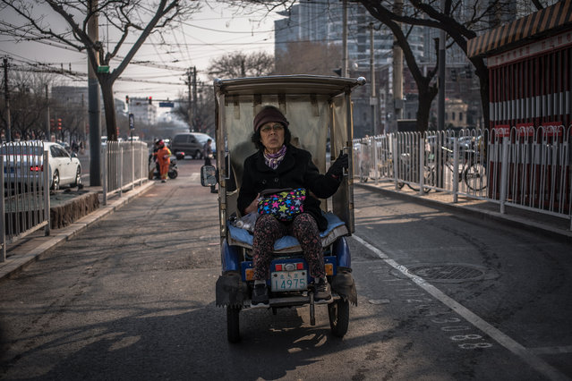 An elderly Chinese woman rides in a three-wheeled motorized auto vehicle, in Beijing, China, 18 March 2019. (Photo by Roman Pilipey/EPA/EFE)