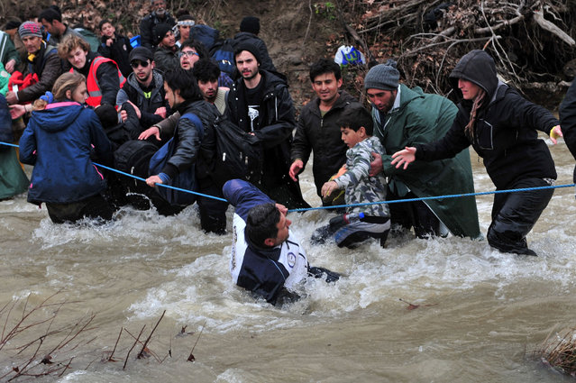 Migrants and refugee cross a river on their way to Macedonia from a makeshift camp at the Greek-Macedonian border, near the Greek village of Idomeni on March 14, 2016, where thousands of them are stranded by the Balkan border blockade. Hundreds of migrants were stopped by Macedonian soldiers after illegally crossing the border from Greece on March 14, an AFP reporter saw. (Photo by Sakis Mitrolidis/AFP Photo)