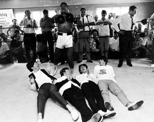 The Beatles, from right to left, Paul McCartney, John Lennon, George Harrison and Ringo Starr pretent to be knocked out by a fake blow from Cassius Clay (Muhammad Ali), lying on the floor of the ring, while visiting the heavyweight contender at his training camp in Miami Beach, Florida, USA, February 18,1964. (Photo by AP Photo)