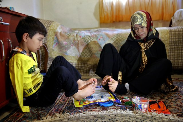 In this picture taken on January 21, 2015, Zohreh Etezadossaltaneh, right, who was born without arms, teaches 9-year old Afghan boy Roohollah Jafar, how to use his feet during a lesson at her home, in Tehran, Iran. (Photo by Ebrahim Noroozi/AP Photo)