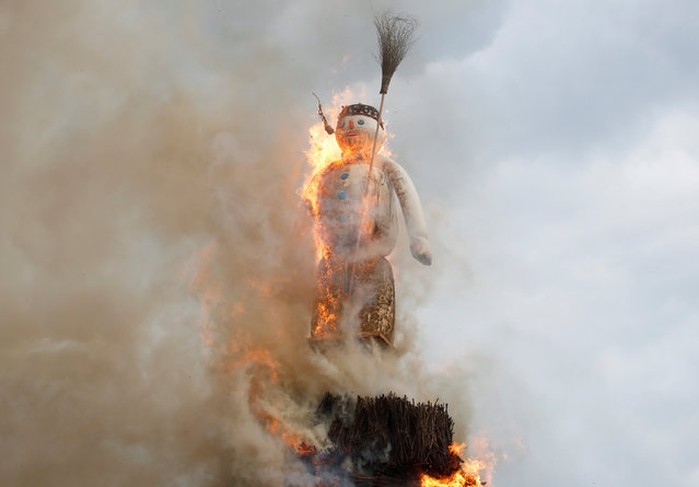 The Boeoegg, a snowman made of wadding and filled with firecrackers, is burning in a bonfire in the Sechselaeuten square in Zurich, Switzerland on April 8, 2019. (Photo by Arnd Wiegmann/Reuters)