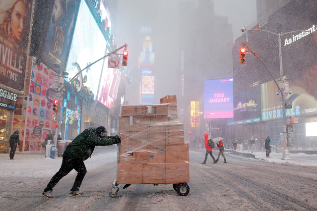 A man attempts to deliver packages in Times Square as heavy snow falls in Manhattan, New York, U.S. February 9, 2017. (Photo by Andrew Kelly/Reuters)