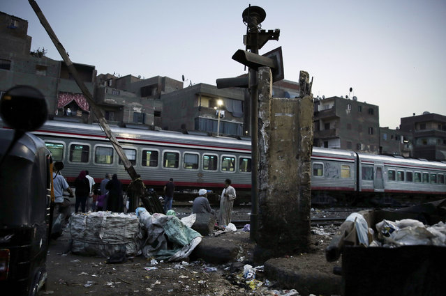 In this October 23, 2018 photo, people wait for the train to pass in Shubra, Cairo, Egypt. A city of 20 million people that combines charm and squalor, Cairo may soon witness an exodus by some of its well-heeled residents, state employees and foreign embassies to a new capital. The new capital – a proper name has yet to be found – is the $45 billion brainchild of general-turned-president Abdel-Fattah el-Sissi, the biggest of the mega-projects he launched since taking office in 2014. (Photo by Nariman El-Mofty/AP Photo)