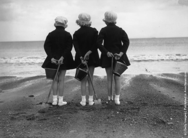 Wearing coats and berets against the chill of an English summer three children have brought their buckets and spades to the beach at Whitby in Yorkshire, 1930