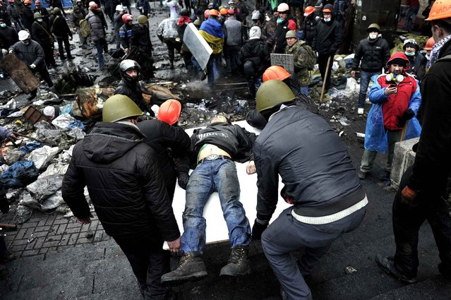 Protesters carry a wounded fellow protester in Kiev on February 20, 2014. Hundreds of armed protesters charged police barricades Thursday on Kiev's central Independence Square, despite a truce called just hours earlier by the country's embattled president. Protesters pushed the police back about 200 metres and were in control of most of the square they had occupied at the start of Ukraine's three-month-old political crisis. (Photo by Louisa Gouliamaki/AFP Photo)