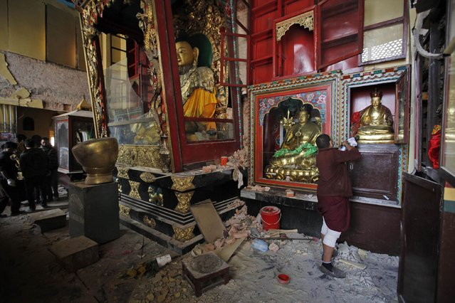 In this Thursday, April 30, 2015 photo, a man looks at a Buddhist God statue inside a monastery near the famous Swayambhunath stupa after it was damaged in the April 25 massive earthquake in Kathmandu, Nepal. Swayambhunath, which dates back to the 5th century, is one of at least 68 cultural heritage sites in Nepal that were damaged by the earthquake. (Photo by Niranjan Shrestha/AP Photo)