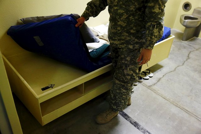 A soldier shows an arrow that points to Mecca inside of sample cell within Joint Task Force Guantanamo's Camp VI at the U.S. Naval Base in Guantanamo Bay, Cuba March 22, 2016. (Photo by Lucas Jackson/Reuters)