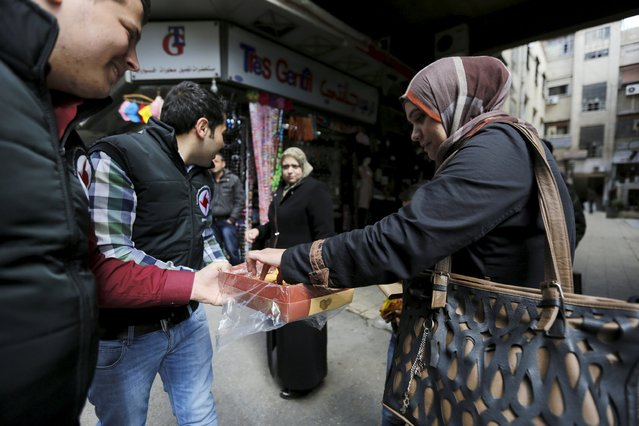 Supporters of the Syrian Social Nationalist party offer traditional arabic sweets to people to celebrate Syrian Mother's Day in the ancient Christian quarter of Bab-Touma in Damascus, Syria March 21, 2016. (Photo by Omar Sanadiki/Reuters)