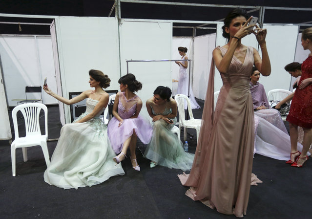 Models take pictures as they prepare in the backstage to display creations by Lebanese international designer Abed Mahfouz during his Spring-Summer 2015 fashion show in Beirut, Lebanon, Wednesday, April 29, 2015. (Photo by Hussein Malla/AP Photo)