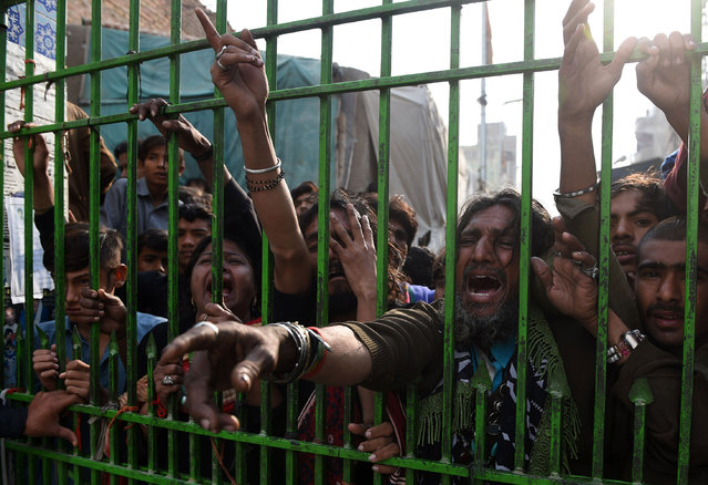 Pakistani devotees react as they gather outside the closed gate of the shrine of 13th century Muslim Sufi saint Lal Shahbaz Qalandar a day after a bomb blew up at the shrine in the town of Sehwan in Sindh province, some 200 kilometres north-east of the provincial capital Karachi on February 17, 2017. Pakistan launched a nationwide security crackdown, officials said, after a bomb ripped through a crowded Sufi shrine, killing at least 70 people including 20 children and wounding hundreds. (Photo by Asif Hassan/AFP Photo)