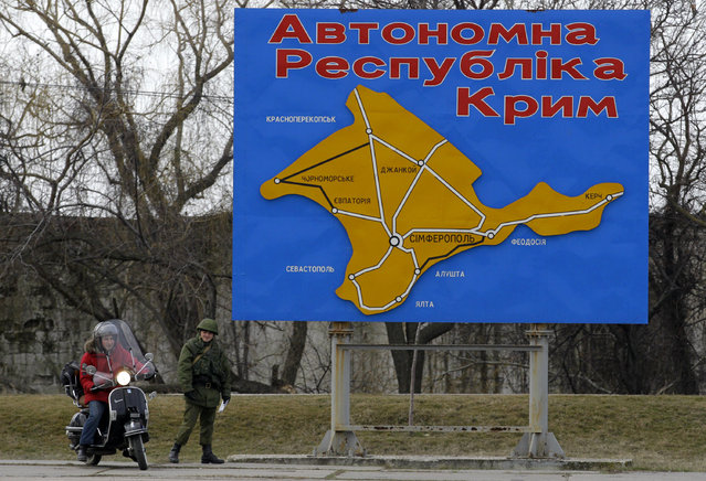 "A pro-Russian soldier stands by a billboard with a map of Crimea and bearing the words ""Autonomous Republic of Crimea"" in the port of Kerch, Ukraine, Monday, March 3, 2014. Pro-Russian troops controlled a ferry terminal on the easternmost tip of Ukraine's Crimea region close to Russia on Monday, intensifying fears that Moscow will send even more troops into the strategic Black Sea region in its tense dispute with its Slavic neighbor. (Photo by Darko Vojinovic/AP Photo)"