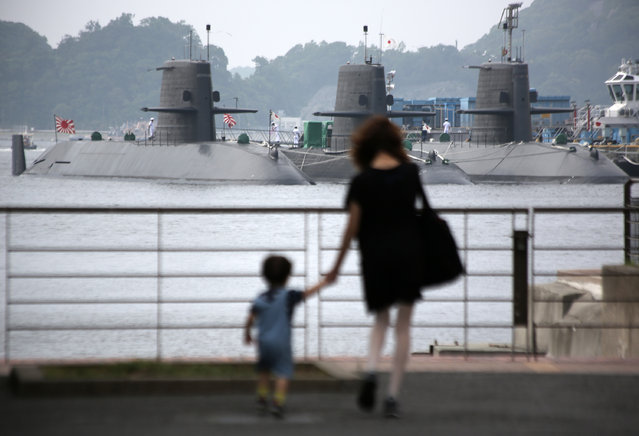 A woman and a child look at submarines of the Japan Maritime Self-Defense Force in Yokosuka, south of Tokyo, Friday, May 15, 2015. (Photo by Eugene Hoshiko/AP Photo)