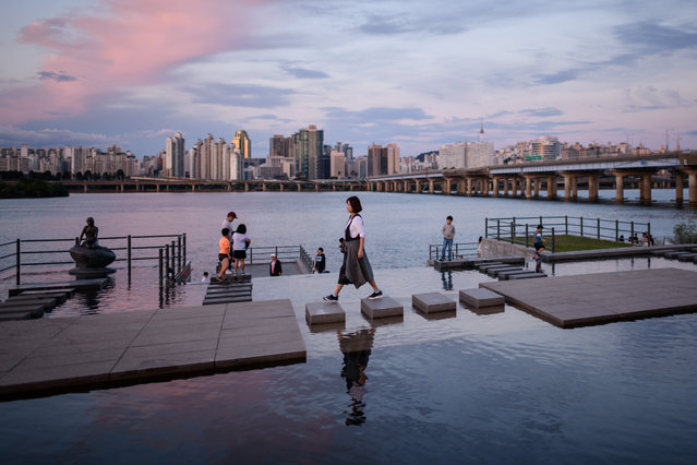 """A woman walks over stepping-stones before the Han river and Seoul's skyline at Yeouido park on September 26, 2018. South Korea is observing the final day of the annual """"Chuseok"""" thanksgiving holiday. (Photo by Ed Jones/AFP Photo)"""