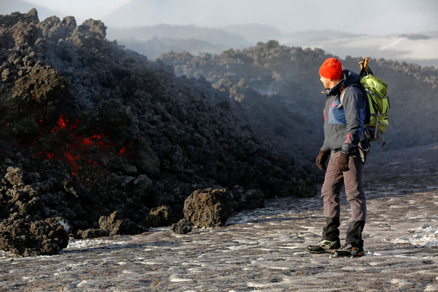 Volcano guide stands in front of lava pouring from Italy's Mount Etna during an eruption on the southern island of Sicily, Italy on March 1, 2017. (Photo by Antonio Parrinello/Reuters)