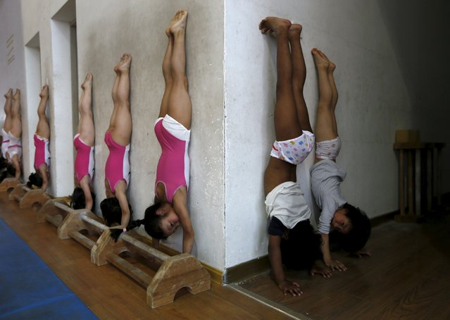 Students practice at the gymnastics hall of a sports school in Jiaxing, Zhejiang province, May 20, 2015. Young gymnasts, from 6 to 11-year-old, train everyday for at least 5-hours. (Photo by William Hong/Reuters)