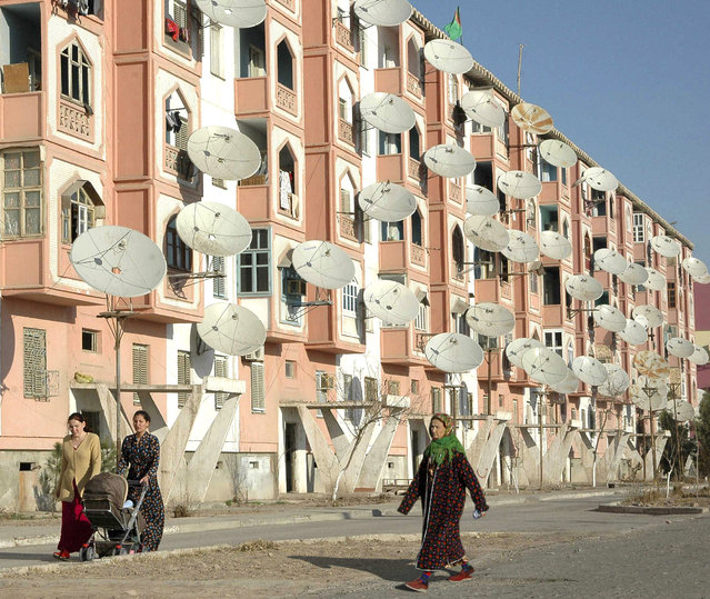 Women walk by a block of flats with satellite TV dishes in the provincial Turkmen city of Turkmenabat March 7, 2007. (Photo by Reuters/Stringer)