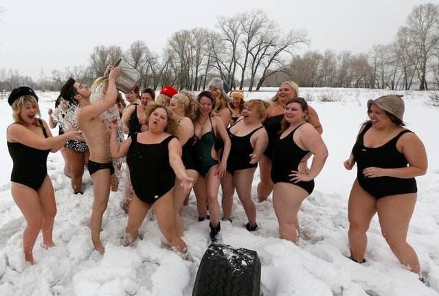 Models of the SibPlus Models agency and participants of the Miss Doughnut beauty competition watch their trainer pouring a bucket of cold water over himself at the Polar Bear winter swimmers club in Krasnoyarsk, Siberia, Russia, March 4, 2017. (Photo by Ilya Naymushin/Reuters)