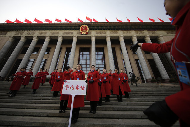 In this Friday, March 3, 2017 photo, a hospitality staffer directs her colleagues posing for photographs outside the Great Hall of the People during the Chinese People's Political Consultative Conference (CPPCC) in Beijing. (Photo by Andy Wong/AP Photo)