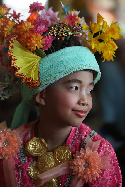 A Tai Yai boy waits for a ceremony to begin at Wat Don Chedi on April 7, 2014 in Mae Hong Son, Thailand. Poy Sang Long is a Buddhist novice ordination ceremony of the Shan people or Tai Yai, an ethnic group of Shan State in Myanmar and northern Thailand. Young boys aged between 7 and 14 are ordained as novices to learn the Buddhist doctrines. It's believed that they will gain merit for their parents by ordaining. (Photo by Taylor Weidman/Getty Images)