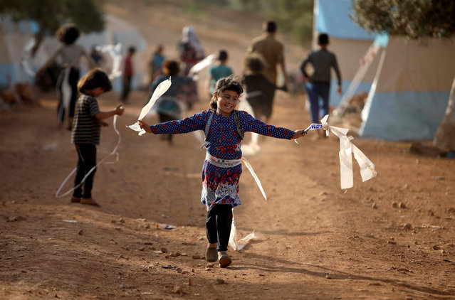 Displaced Syrian children play in a camp for internally displaced people near Kah, in the northern Idlib province near the border with Turkey on June 3, 2019 on the eve of Eid al-Fitr, which marks the end of the Muslim holy fasting month of Ramadan. The conflict in Syria has killed more than 370,000 people and displaced millions since it started in 2011. (Photo by Aaref Watad/AFP Photo)