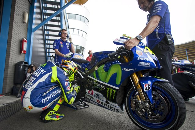 Yamaha MotoGP rider Valentino Rossi of Italy kneels next to his bike before a warm up session at the TT Assen Grand Prix at Assen, Netherlands June 27, 2015. (Photo by Ronald Fleurbaaij/Reuters)