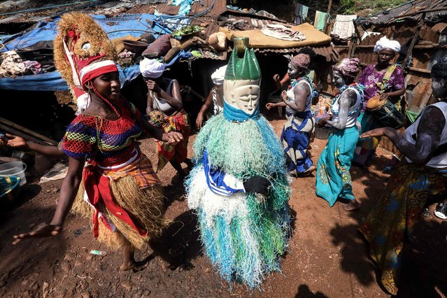 Bondo women's secret society dance during a performance in Kroo Bay, Freetown on November 24, 2018. In the center of the circle, in the blue and green regalia is the Bondo Devil named Mama Salone whose appearance often symbolises new initiates in the secret society bush. Fatmata Bangura, the young women dancing beside the devil wearing a red hat with a looking glass upon it is called a Sampa-Bondo. (Photo by Lynn Rossi/AFP Photo)