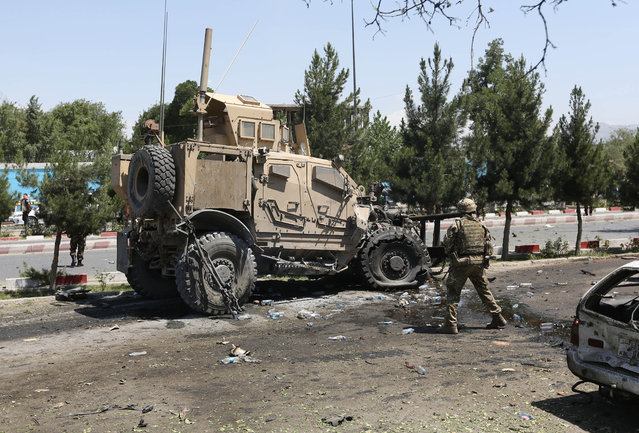 A NATO soldier walks near a damaged vehicle at the site of a suicide attack on a NATO convoy in Kabul, Afghanistan, Tuesday, June 30, 2015. It comes a week after an audacious attack on the nation's parliament, which highlighted the ability of insurgents, who have been fighting to overthrow the Kabul government for almost 14 years, to enter the highly fortified capital to stage deadly attacks. (Photo by Rahmat Gul/AP Photo)