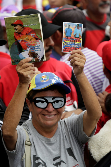 A supporter of Venezuela's President Nicolas Maduro wearing glasses with the eyes of Venezuela's late President Hugo Chavez, holds postcards with pictures of them, during a rally to commemorate May Day, in Caracas, Venezuela, May 1, 2016. (Photo by Marco Bello/Reuters)