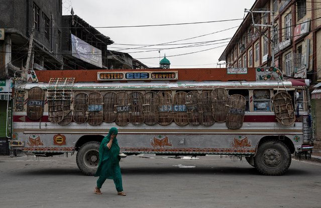 A Kashmiri woman walks past a bus used as a road block by Indian security personnel during restrictions after the scrapping of the special constitutional status for Kashmir by the government, in Srinagar, August 11, 2019. (Photo by Danish Siddiqui/Reuters)