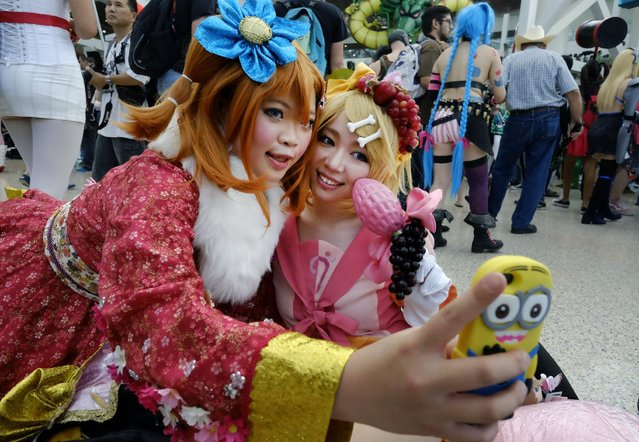 Fans in costumes take a selfie at the 24th annual Anime Expo held at the Los Angeles Convention Center on Friday, July 3, 2015, in downtown Los Angeles. The expo, which celebrates Japanese animation and comic book culture, runs July 2-5, 2015. (Photo by Richard Vogel/AP Photo)