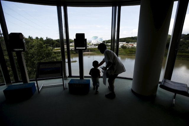 A family looks at Kyushu Electric Power's Sendai nuclear power station from the visitor's center in Satsumasendai, Kagoshima prefecture, Japan, July 8, 2015. (Photo by Issei Kato/Reuters)