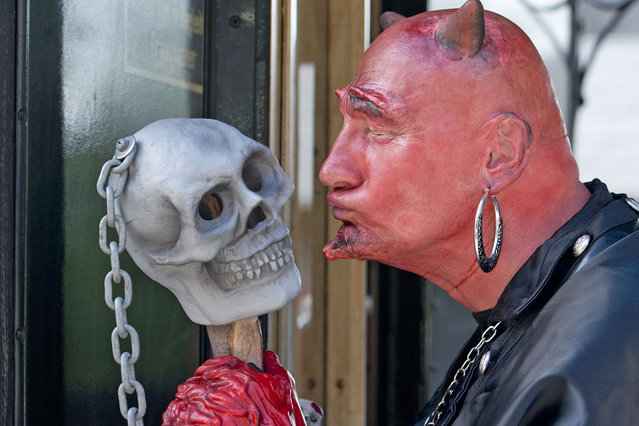 A men costumed as devil kisses a skull in a small train in Wernigerode, Germany, Wednesday, April 30, 2014. Hundreds of costumed devils and witches meet to celebrate Walpurgis Night, a traditional religious holiday of pre-Christian origins. The event is named after St. Walburga, an English nun who helped convert the Germans to Christianity in the 8th century. (Photo by Jens Meyer/AP Photo)