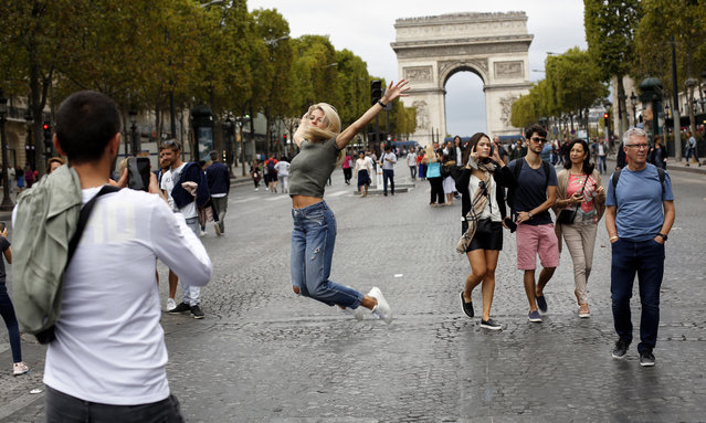 """A woman jumps for a picture on the champs Elysees avenue, during the """"day without cars"""", with the Arc de Triomphe in background, in Paris, Sunday, September 22, 2019. It is the fourth year the city has held a car free day in an attempt to ease air pollution. (Photo by Thibault Camus/AP Photo)"""