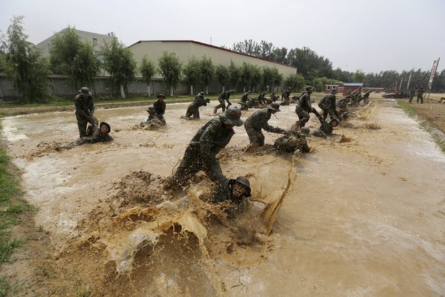 Paramilitary policemen practise combat skills in a muddy pond during a training session at a military base in Beijing, China, July 10, 2015. (Photo by Reuters/Stringer)