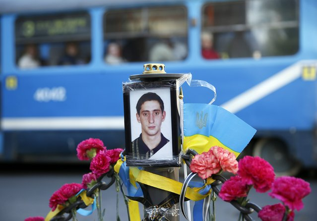 A tram passes a portrait of Andriy Biryukov, a pro-Ukrainian activist killed in clashes on Friday, at his funeral in Odessa May 6, 2014. Pro-Russian rebels shot down a Ukrainian helicopter in fierce fighting near the eastern town of Slaviansk on Monday, and Kiev drafted police special forces to the southwestern port city of Odessa to halt a feared westward spread of rebellion. (Photo by Gleb Garanich/Reuters)