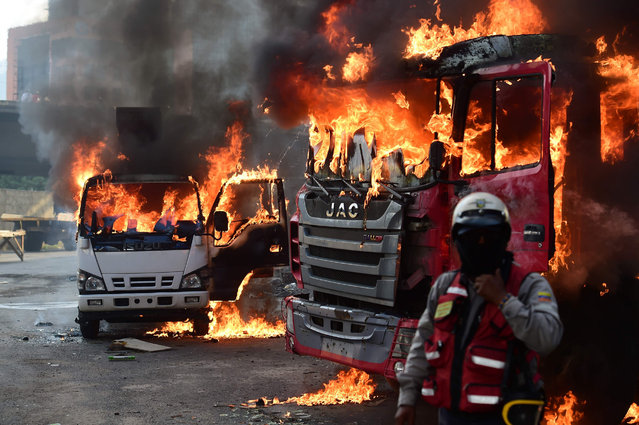 Trucks burn in flames during a demonstration by Venezuelan opposition activists against President Nicolas Maduro in Caracas, on April 24, 2017. Protesters rallied on Monday vowing to block Venezuela's main roads to raise pressure on Maduro after three weeks of deadly unrest that have left 21 people dead. Riot police fired rubber bullets and tear gas to break up one of the first rallies in eastern Caracas early Monday while other groups were gathering elsewhere, the opposition said. (Photo by Ronaldo Schemidt/AFP Photo)