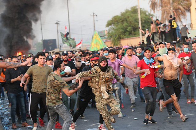 Anti-government protesters help a soldier from the Federal Police Rapid Response Forces to get out of the protest site area after other protesters beat him, in Baghdad, Iraq, Thursday, October 3, 2019. Iraqi security forces fired live bullets into the air and used tear gas against a few hundred protesters in central Baghdad on Thursday, hours after a curfew was announced in the Iraqi capital on the heels of two days of deadly violence that gripped the country amid anti-government protests that killed over 19 people in two days. (Photo by Hadi Mizban/AP Photo)