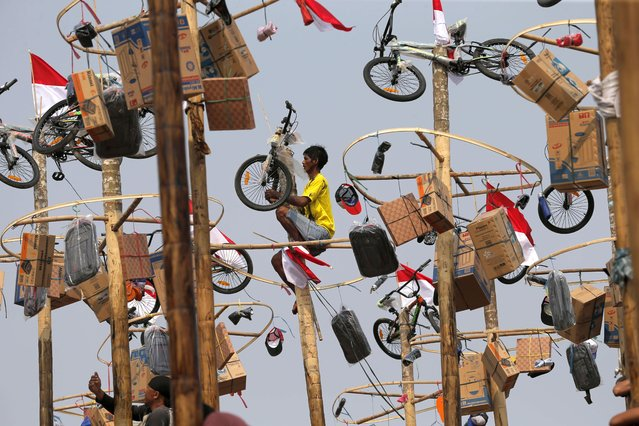 An Indonesian man retrieves his prize after climbing up a greased pole during a greased-pole climbing competition held as part of Independence Day celebrations at Ancol Beach in Jakarta, Indonesia. Saturday, August 17, 2019. Indonesia is celebrating its 74th anniversary of independence from the Dutch colonial rule. (Photo by Tatan Syuflana/AP Photo)