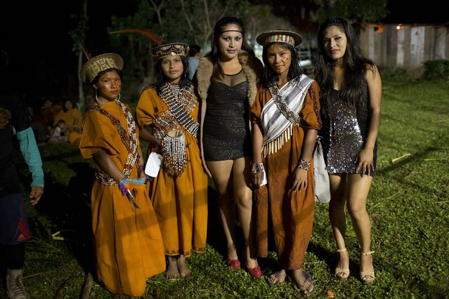In this June 23, 2015 photo, Ashaninka Indian beauty contestants pose for a photo with members of a visiting music group, hired to perform during the annual founding anniversary festivities, in Otari Nativo, Pichari, Peru. The contestants wear the simple brown dresses of the Ashaninka woman, their faces dotted in a traditional design with a red dye extracted from a spice called achiote. (Photo by Rodrigo Abd/AP Photo)