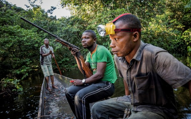 Mohamed Esimbo Matongu, Sadate and Papy return to their campsite empty-handed after a night hunting in the forest near the city of Mbandaka, Democratic Republic of the Congo, April 3, 2018. (Photo by Thomas Nicolon/Reuters)